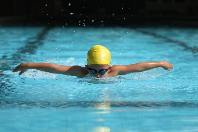 close up of a caucasian child competing in a swimming race.