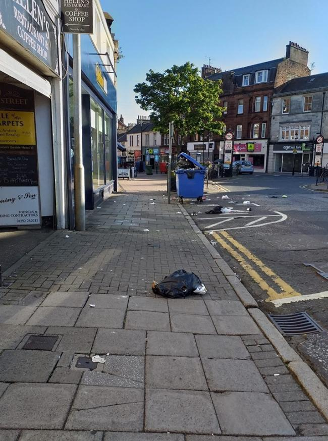 The bin can be seen overflowing with rubbish strewn onto the road