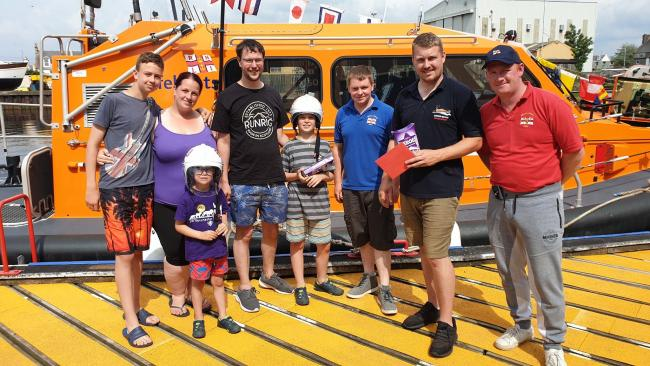 Andrew McNicol, fifth from the left pictured with his mum and members of the lifeboat crew at Girvan. Right, the air ambulance arrives.