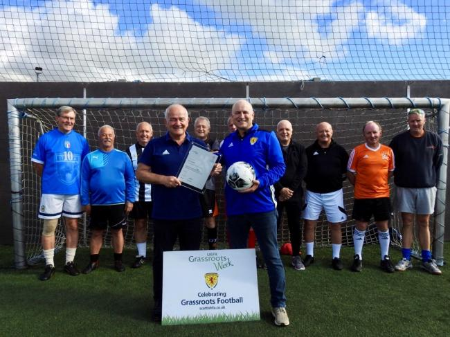 Gary is pictured with his honour as Walking Football particpathns look on.