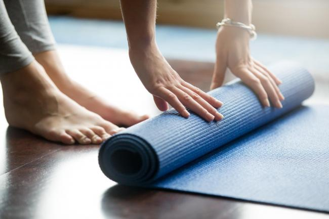 Close-up of attractive young woman folding blue yoga or fitness mat after working out at home in living room. Healthy life, keep fit concepts. Horizontal shot.