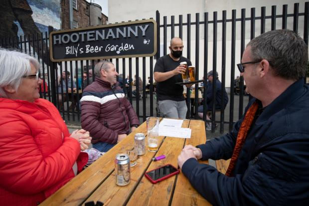 Ayr Advertiser: Members of the public enjoy their first drink in a beer garden at the Hootenanny, Glasgow.