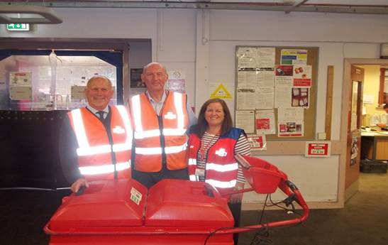 John Scott with postman John Price and manager Theresa Cunningham .